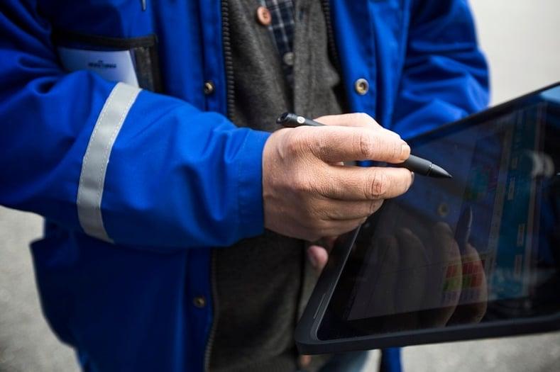 Työntekijä käyttää tabletin ruudulla näkyvää ohjelmaa