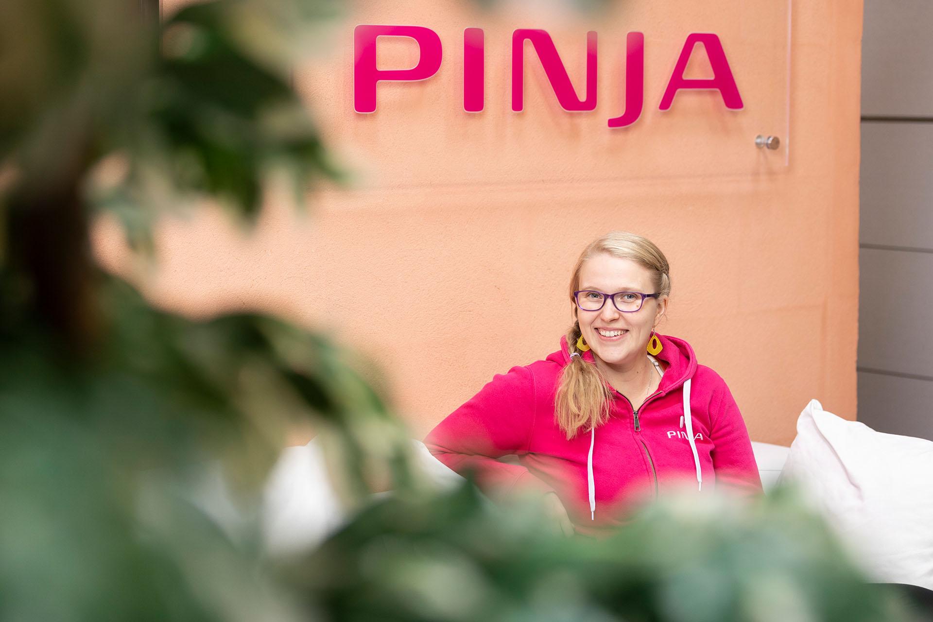 Service desk työntekijä Paula Huuskonen Pinjan hupparissa istumassa valkoisella sohvalla Pinjan kyltin alla