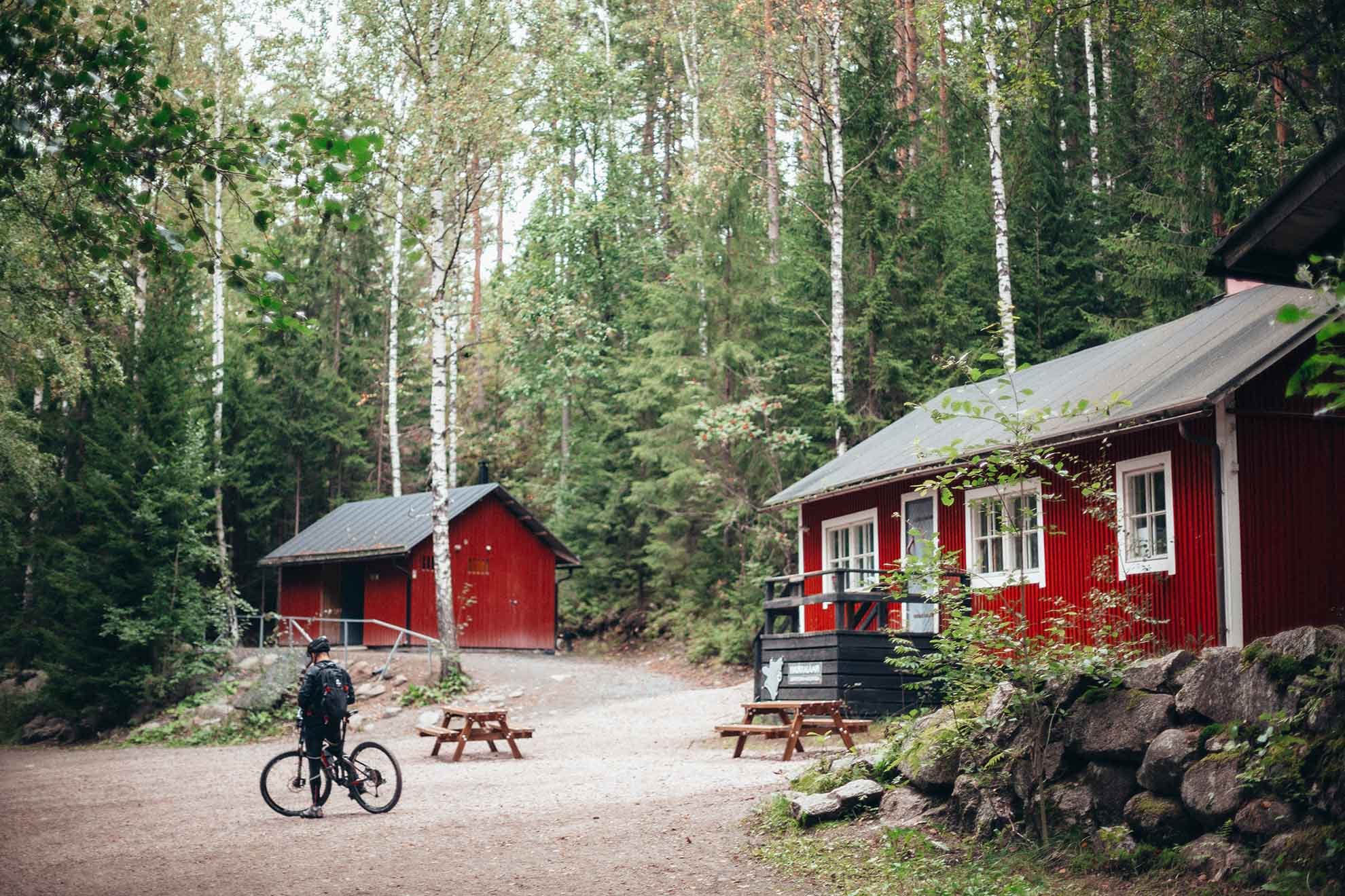 A red summer cottage with a cyclist in the yard