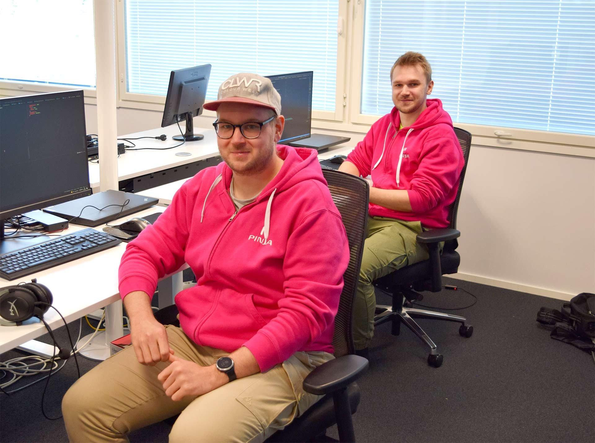 Miehet istuvat työpöytien ääressä