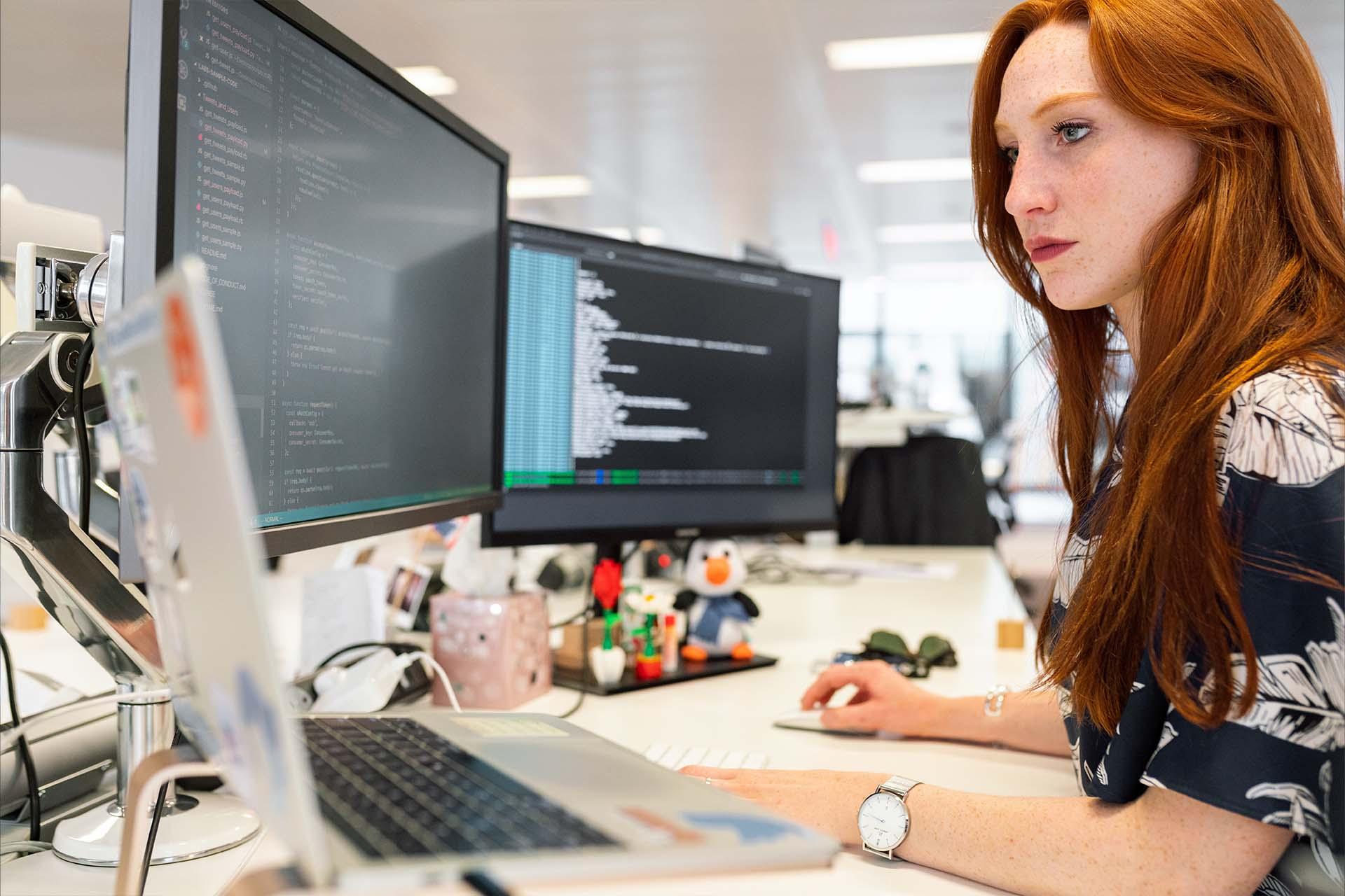 Punahiuksinen nainen kahden näytön ja kannettavan tietokoneen äärellä ohjelmoimassa